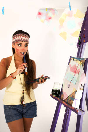 lectern: young girl with a headband painting at an indoor white room with a brush in her mouth, looking at the lectern where there is a draw she is working on  In the background, there are a couple of paints she made already and they are hanging up from a rope wit