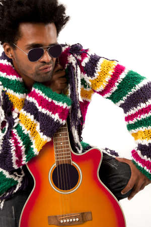A black man young and handsome with an orange and acustic guitar in one hand, wearing a colorful cout and blue jeans, looking over his shoulder at the right with sunglasses photo