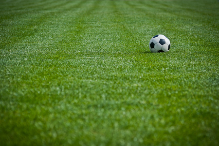 Football field and soccer ball on green grass  photo