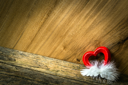 Heart and feather on wooden background. Insert your text. photo