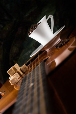 coffee beans with  coffee cup and cane sugar on a guitar photo