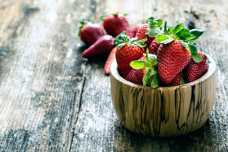 wooden bowl of fresh strawberries on old wooden table photo