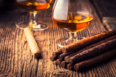 cigar smoke: quality cigars and cognac on an old wooden table Stock Photo