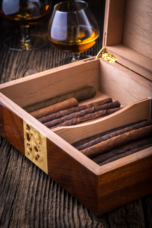 humidor with quality cigar and cognac on an old wooden table Stok Fotoğraf