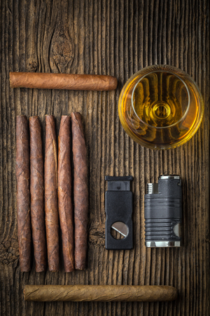 glass cutter: quality cigars and cognac on an old wooden table Stock Photo