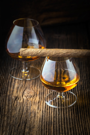 quality cigars and cognac on an old wooden table photo