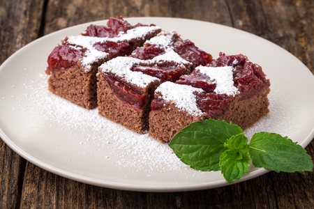 sliced piece of plum cake with cocoa sprinkled with sugar