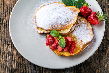 maple syrup: filled with homemade pancakes with strawberries and maple syrup Stock Photo