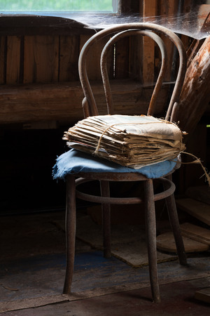pile of newspapers: a pile of old newspapers tied with twine on a chair