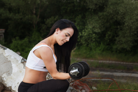 girl working out: Pretty young fitness girl working out with dumbbell. Stock Photo