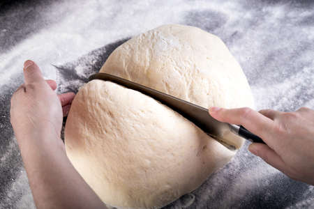 pizza dough: Cutting dough with knife on small portion for pizza dough. Stock Photo