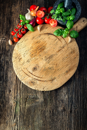 trompo de madera: tabla de madera con verduras, hierbas y una picadora de piedra Foto de archivo