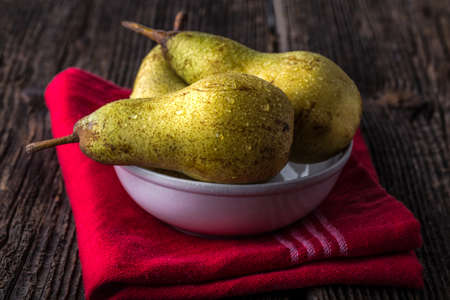 dewy: dewy fresh pears in a bowl on old wooden table