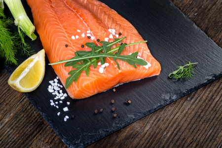 salmon filet: Salmon filet with lime, salt, pepper, rucoli,fennel and rosemary on black plate ready to cook. Stock Photo