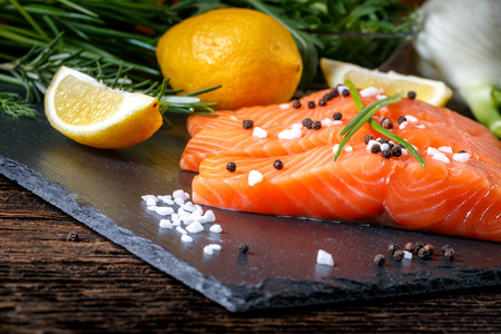salmon filet: Salmon filet sliced on three parts  with lime, salt, pepper, rucoli,fennel and rosemary,  ready to cook. Stock Photo
