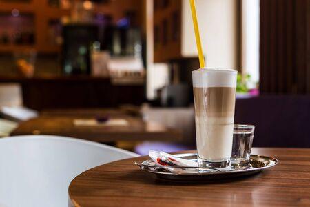 Kaffee latte in einem Café. Milchschaum. Tack. Etwas Wasser und relax.Coffee Shop.