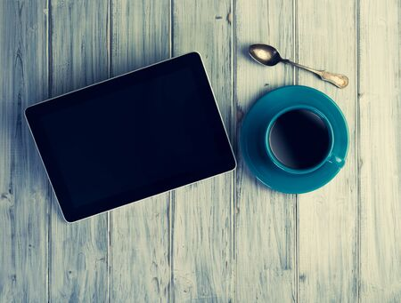 coffeetime: Coffee and tablet on the table. Pause and coffeetime. Blue cup and background.