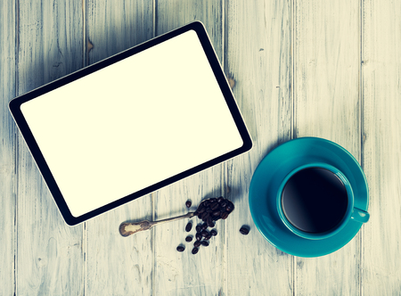 coffeetime: Coffee and tablet on the table. Pause and coffeetime. Blue cup and mocup pad.