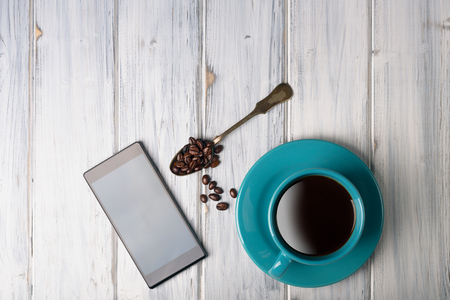 coffeetime: Coffee and smart phone on the table. Pause and coffeetime. Blue cup and background.
