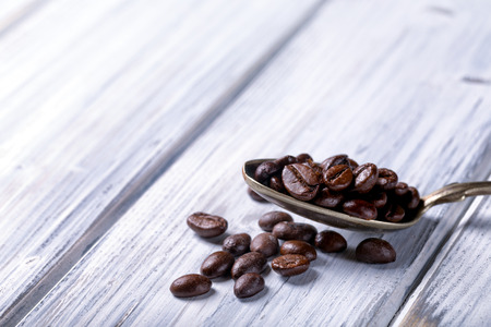 coffeebeans: Silver spoon with coffee beans. White rural background. Brown coffeebeans.