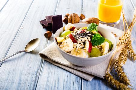 Oatmeal with yoghurt, apple, banana, grape and chia seeds. Bowl of fresh fruit.