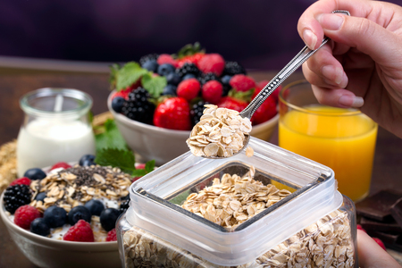 oatmeal bowl: Spoon of oatmeal. Bowl with berries. Selective focus.