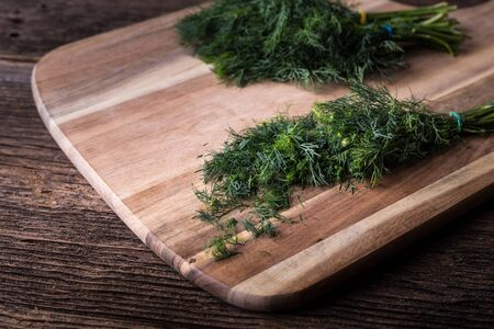 Sliced twig of dill on a wooden board. Branch seasoning aromatic spice.