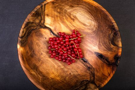 Bunch of red currants in a bowl from walnut wood. Healthy fruit with antioxidant.