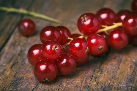 detail of bunch: Detail bunch of red currants on a old wooden table. Healthy fruit with antioxidant. Stock Photo