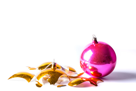 crashed: Broken old vintage Christmas ball on white backgroound. Crashed yellow and pink bauble.