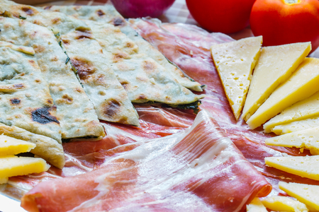 Croatian typical traditional food, soparnik and prosciutto and cheese.