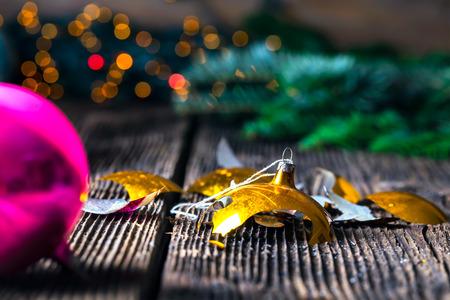 Broken old vintage Christmas ball on wooden table. Christmas lights and Christmas tree.