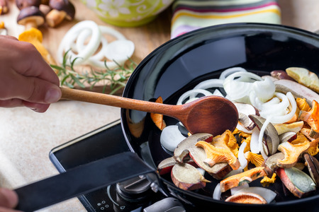 Frying pan with boletus, chanterelle and onion. Cooking musrooms. Tasty meal.