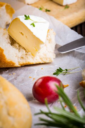 Cheese with white mold. Camembert or brie type. Radish, grapes and baguette. Healthy breakfast. Stock Photo