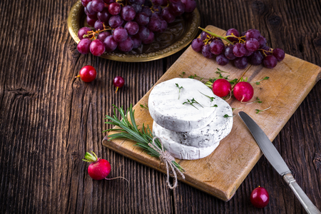 Cheese with white mold. Camembert or brie type. Radish, rosemary and grape. Healthy breakfast.