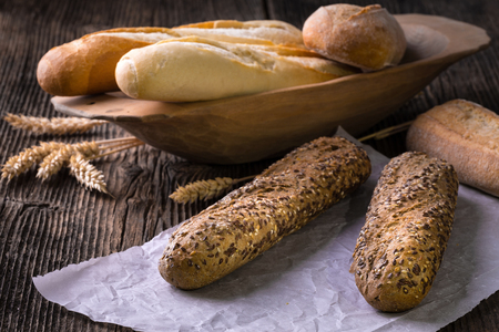 Fresh cereal pastry. Freshly baked white and brown baguette with wheat ears and grain.