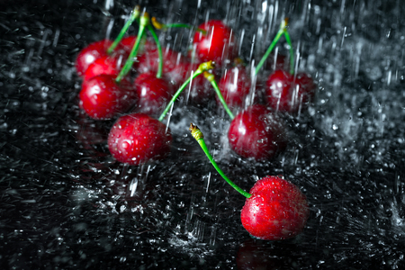 wash: Group of cherries with falling water drops. Fresh fruit on black glass.