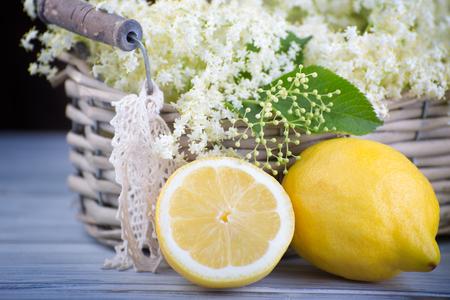 Fresh nigra sambucus in the wooden basket with yellow lemons.