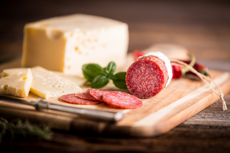 Dry salami or sausage with cheese, bread and herbs.