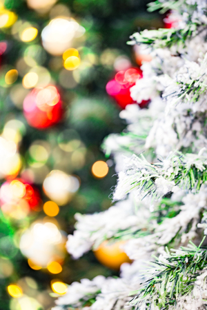 Synthetic christmas tree with snowflakes and decorations in the background. Stock Photo