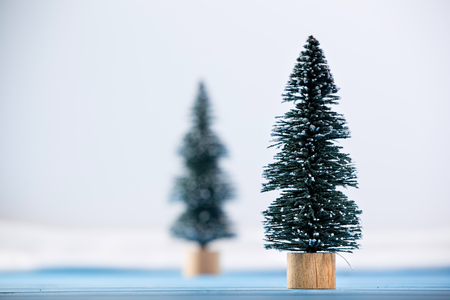 Miniature toy Christmas tree on a wooden table. Imitation realistic scene.