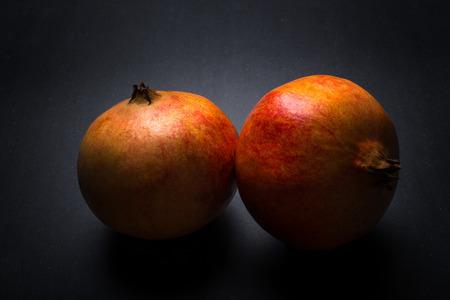 Fresh pomegranate on the dark background. Reklamní fotografie