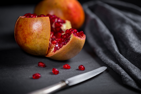 Sliced pomegranate with juicy red grains and knife.