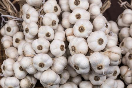 Braid of a organic homemade garlic. Strings of dried garlic in a market. Reklamní fotografie