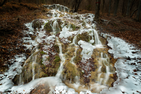 Frozen wild waterfall in the mountains of central Europe