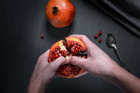 Sliced pomegranate with juicy red grains and spoon.