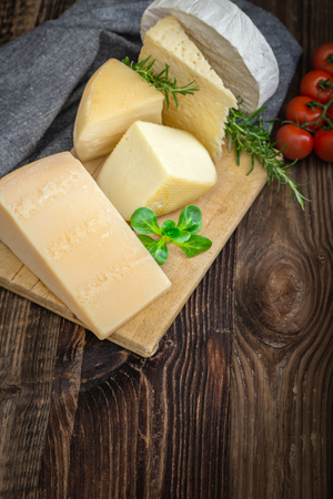 Bunch of fresh  high - quality cheeses from dairy with basil, rosemary and tomatoes. Reklamní fotografie