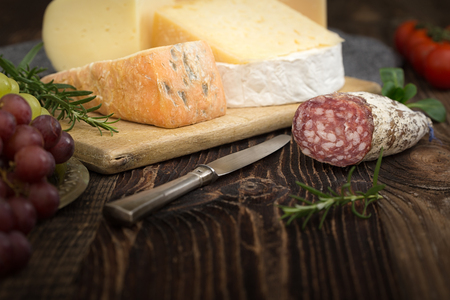 Bunch of fresh  high - quality cheeses from dairy with basil,rosemary, tomatoes, grapes and salame. Stock Photo
