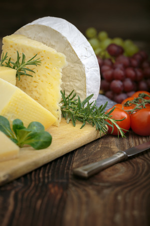 Bunch of fresh  high - quality cheeses from dairy with basil,rosemary, tomatoes and grapes.