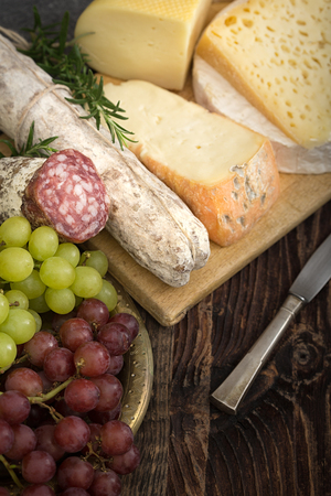 Bunch of fresh  high - quality cheeses from dairy with basil,rosemary, tomatoes, grapes and salame. Reklamní fotografie